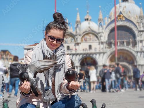 Foto op Plexiglas Venetie Young female traveler sitting and feeding pigeons on the Piazza San Marco
