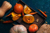 Variety of pumpkins of different size, form and color on a tray on rustic textured blue background. Top view. - 176831845