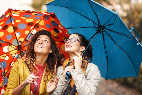 Juliste Two female best friend walks at the city street with umbrellas above head