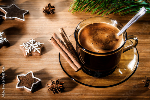 Wooden background with Christmas cookies and a cup of coffee with cinnamon sticks. Still life, view from the top of the New Year's gingerbread.