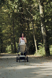 Attractive woman pushing a baby stroller along a rural road - 176839437