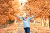 glückliche Seniorin beim Ausflug in der Herbstallee - 176839872