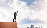 Businessman looking down from roof and modern cityscape at background. Mixed media - 176840899