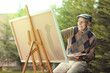 Elderly man painting on a canvas outside - 176841609