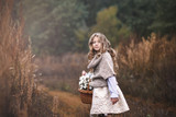 A beautiful little girl with a basket of wildflowers in her hand goes on a field road towards the forest. - 176842097