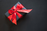Gift box in black paper with red ribbon on black surface. Top view.