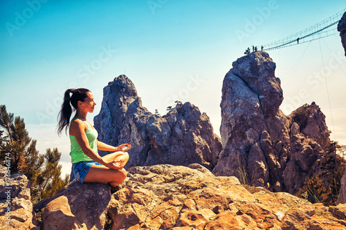 Fotobehang School de yoga Woman with arms raised sitting on mountain by cloudscape
