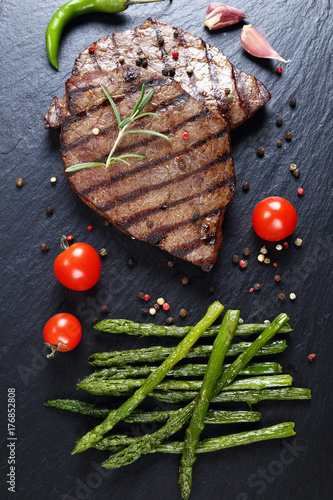 Fotobehang Steakhouse beef steaks with asparagus on stone