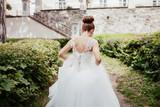 Bride without veils walks near the castle