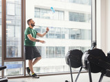 Man in a gym throwing a bottle up in the air. - 176868221