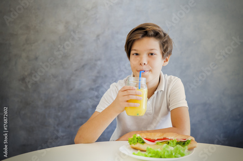 Wall mural Portrait of cute teen boy having breakfast at home