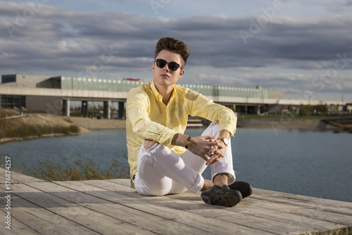 Handsome young man wearing jeans and sunglasses Poster