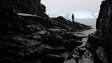 The tourist is standing on rocks against the background of the bay and icebergs. Andreev. - 176875671