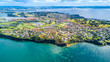 Aerial view on residential suburbs surrounded by sunny ocean harbour. Whangaparoa peninsula, Auckland, New Zealand - 176885668