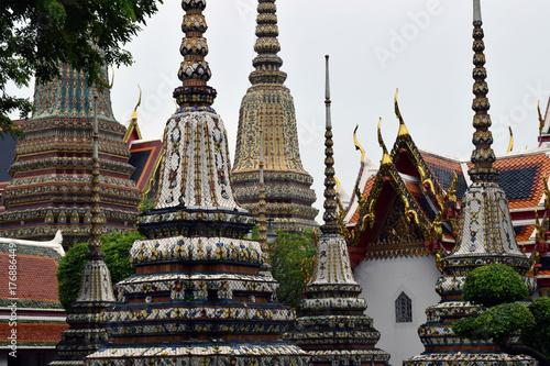 Cupulas de chedis adornados con piedras preciosas en un patio de templo de Taila Poster