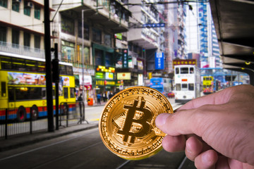 Hand holding a bitcoin with vibrant Hong Kong in the background.