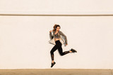 Full length portrait of young healthy fitness woman in sport wear jumping near white wall - 176892276