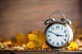 Vintage alarm clock and maple tree leaves