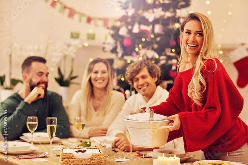 Group of family and friends celebrating Christmas dinner плакат