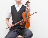 A boy teenager plays an old violin. Training. Education. School. Aesthetic training. Elementary classroom. - 176896455