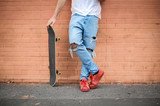 Skater guy standing in front of a brick wall - 176896473