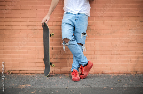 Skater guy standing in front of a brick wall Plakát