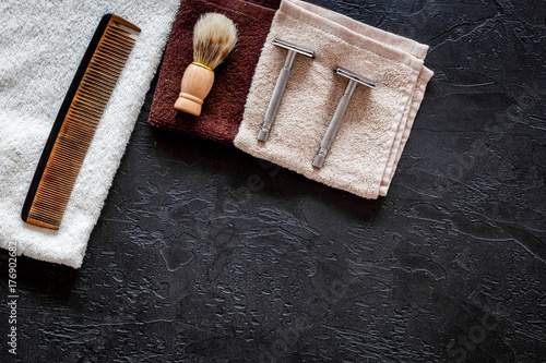 At the barbershop. Razors, shaving brush, comb and towel on black background top view copyspace