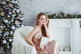 Holidays, celebration and people concept - young woman in elegant dress over christmas interior background. Image with grain - 176903466