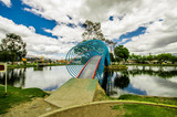 Beautiful colorful bridge over an artificial lake located in the midle of a park with the reflection in the water, in the city of Cayambe, Ecuador