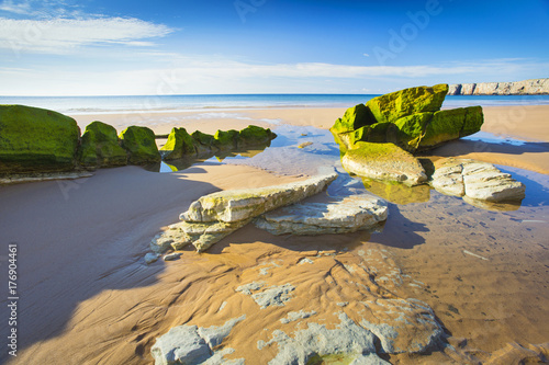 Foto op Aluminium Strand stones and shadows on the golden beach in Portugal