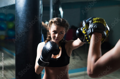 Young fighter boxer fit girl wearing boxing gloves in training with personal trainerin gym Poster