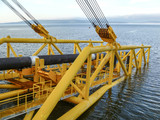 Laying of pipes with pipe-laying barge crane near the shore. Des - 176931026