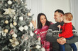 A fun , happy family with Christmas gifts. Parents and little baby having fun near the Christmas tree in the room. Loving family by the Christmas tree