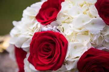 His and hers wedding rings on bridal bouquet of red roses and white hydrangeas.