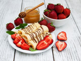 crepes with strawberries and chocolate sauce - 176943876