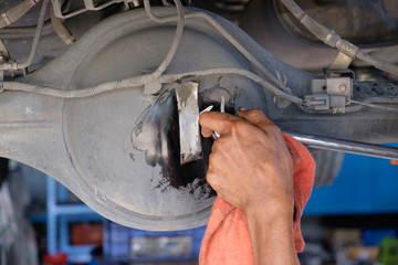 A man maintenance truck differential, changing  differential oil.