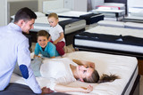 Young happy woman with husband and sons lying on back on tested mattress in store - 176945402