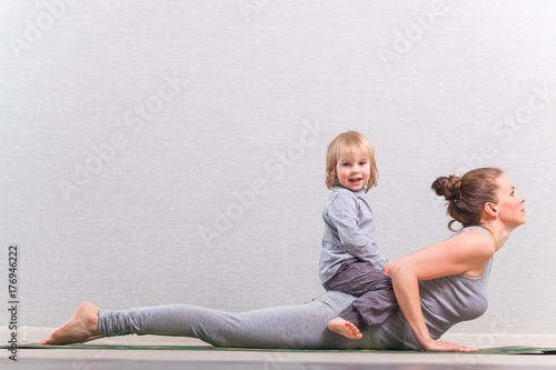 Plakat hatha yoga exercises mom with child practicing at home