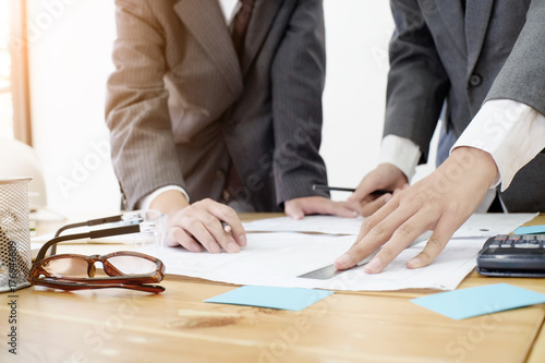 Fototapeta architectural drawing a two business man drawing construction blue print in office.