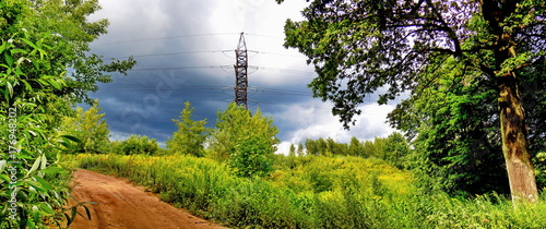 Unpaved road, electricity pylon and thunderclouds  - 176948202