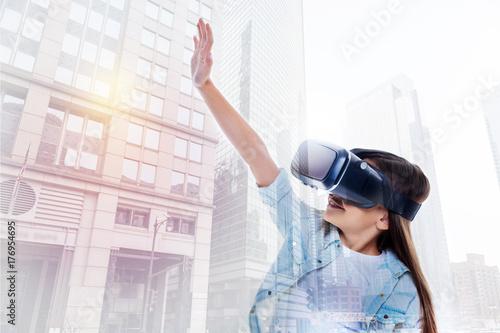Cute little girl in VR headset raising a hand