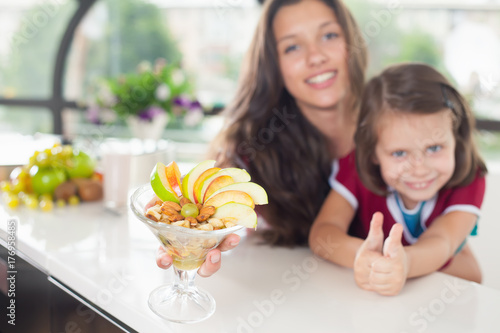 Cute little girl cooking with her mother, healthy food