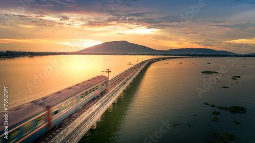Pociąg pracował z dużą prędkością przez most kolejowy Nad jeziorem Pa Sak Dam Lopburi Tajlandia Piękny zachód słońca