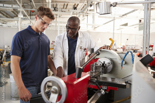 Fridge magnet Engineer showing male apprentice how to operate machinery, close up