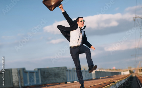 The joy of success. Young lucky businessman on railway platform.Businessman in suit happily runs and throws his suitcase. - 176981055
