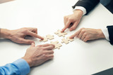 business cooperation concept - businessmen's  connecting puzzle pieces - 176983081