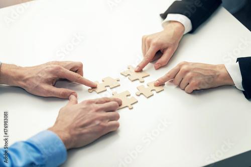 business cooperation concept - businessmen's connecting puzzle pieces