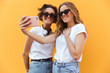 Two cheery young teenage girls in sunglasses taking a selfie