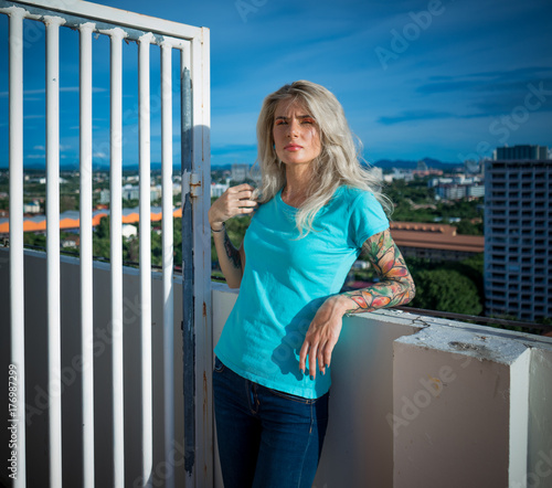 Summer portrait of young beautiful blonde on the roof of a tall building. Wearing a turquoise tshirt and jeans. Arms tattooed.