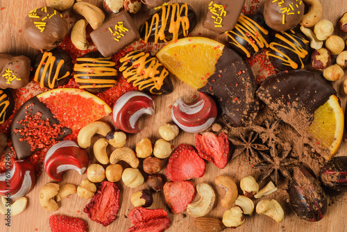 Wall mural Chocolate sweets with orange slices and dried fruits on a wooden table. handmade?